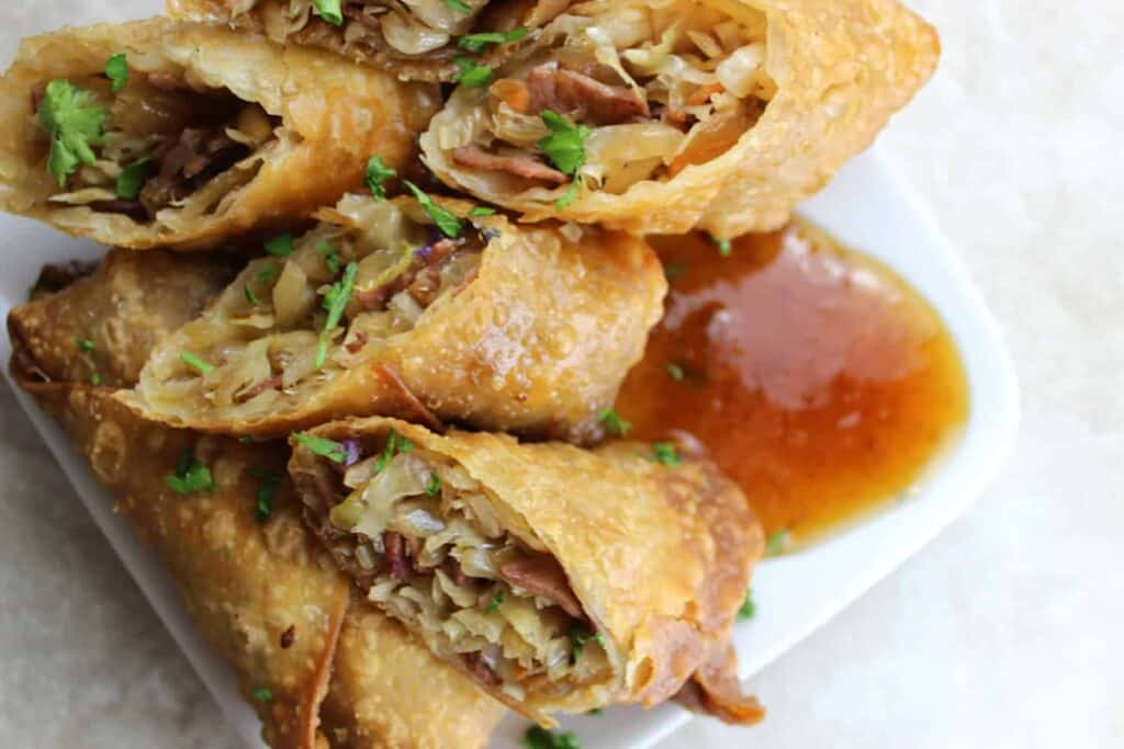 egg rolls on a plate with sauce