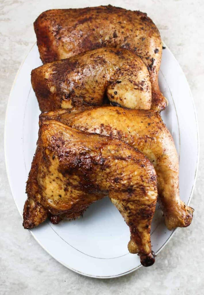 smoked chicken quarters on a platter