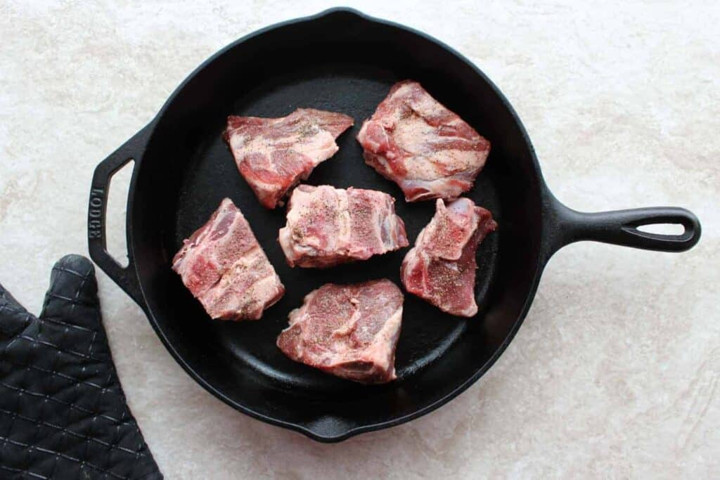 raw lamb with salt and pepper in the pan