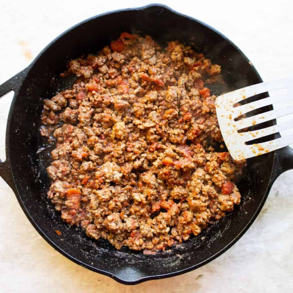 taco meat in a cast iron skillet with a spatula