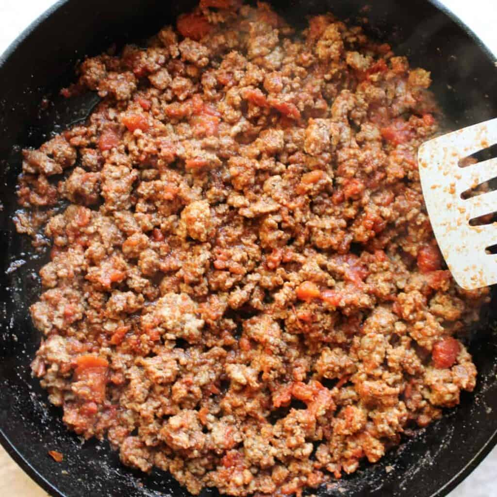 coked taco meat in a cast iron skillet with a spatula