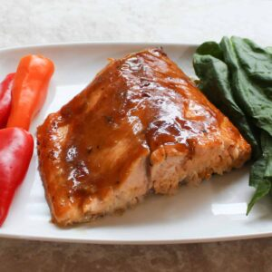 apricot and mustard glazed salmon on a plate with peppers and spinach
