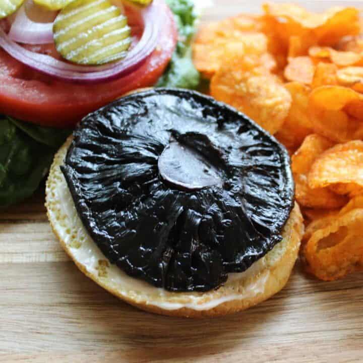 portobello mushroom cap sandwich on a bun with lettuce tomato onion and pickle