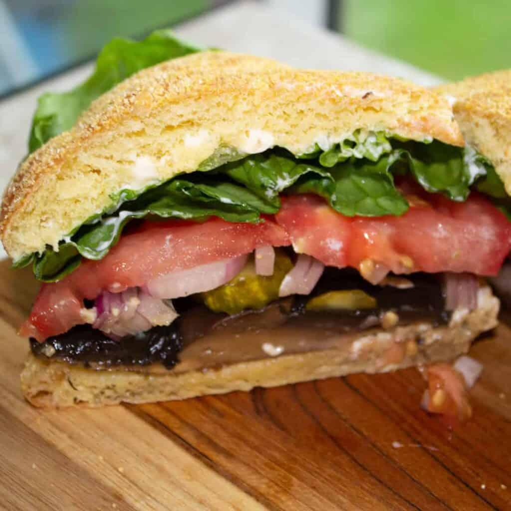 portobello mushroom cap sandwich with lettuce onion and pickle