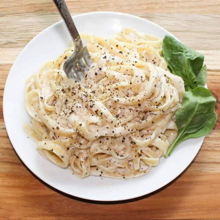 alfredo sauce with a fork and spinach