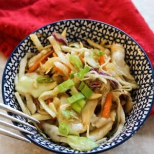 asian slaw in a bowl with a red napkin