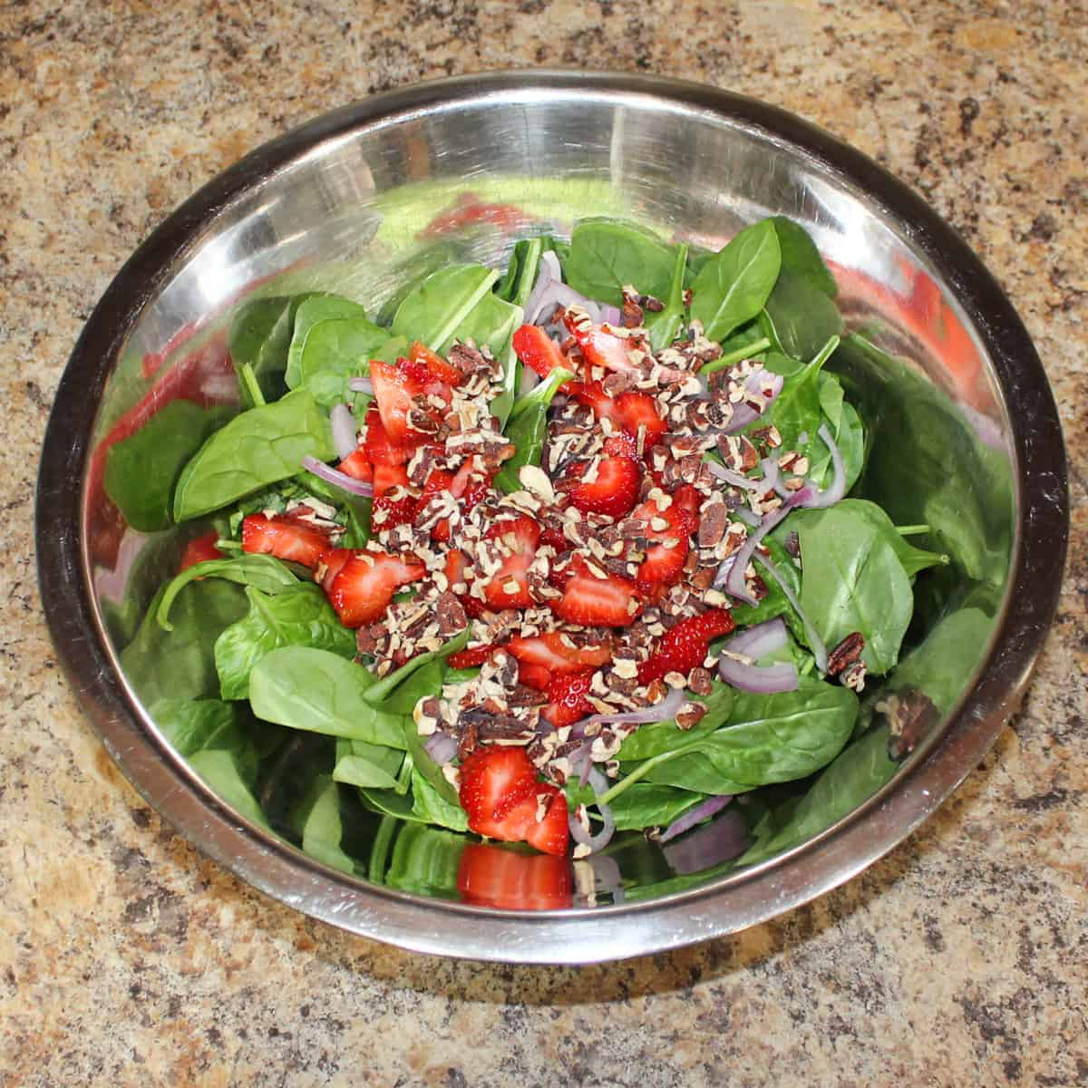 strawberry spinach salad in a bowl without dressing