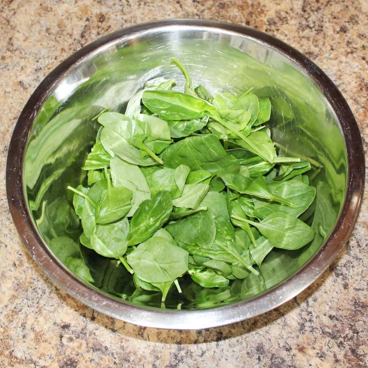 fresh spinach in a silver bowl