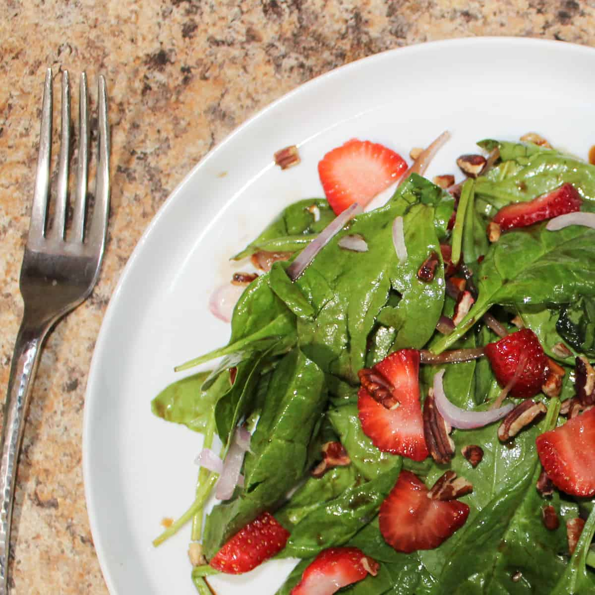 strawberry spinach salad on a plate with a fork